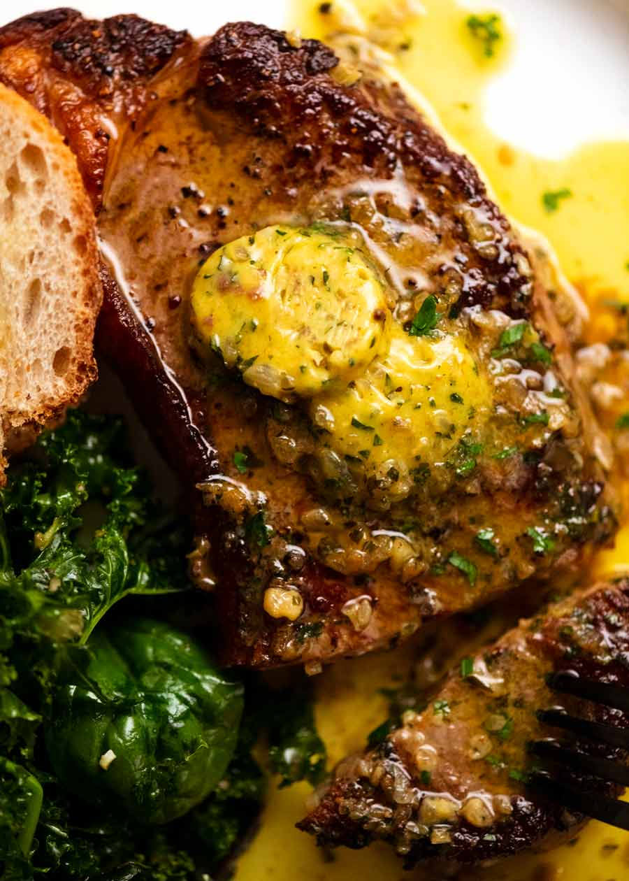 Cafe de Paris butter on steak on a plate, ready to be eaten
