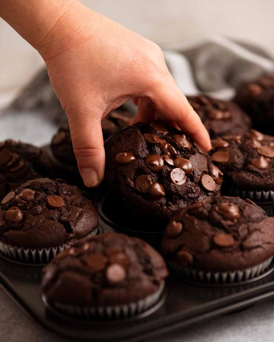 Hand reaching for Chocolate Muffins