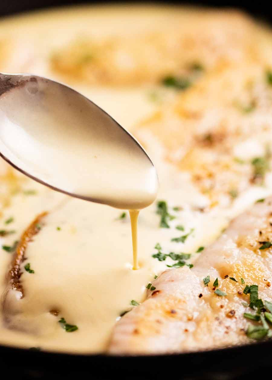 Close up of drizzling white wine sauce