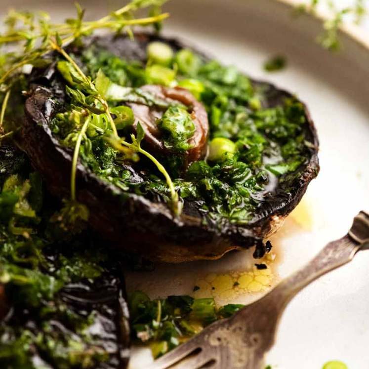 Roasted Large Mushrooms with Green Onion Thyme Butter on a plate, ready to be eaten