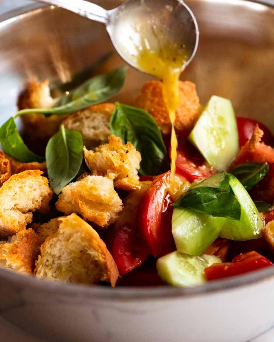 Drizzling dressing over Panzanella - Italian tomato and bread salad