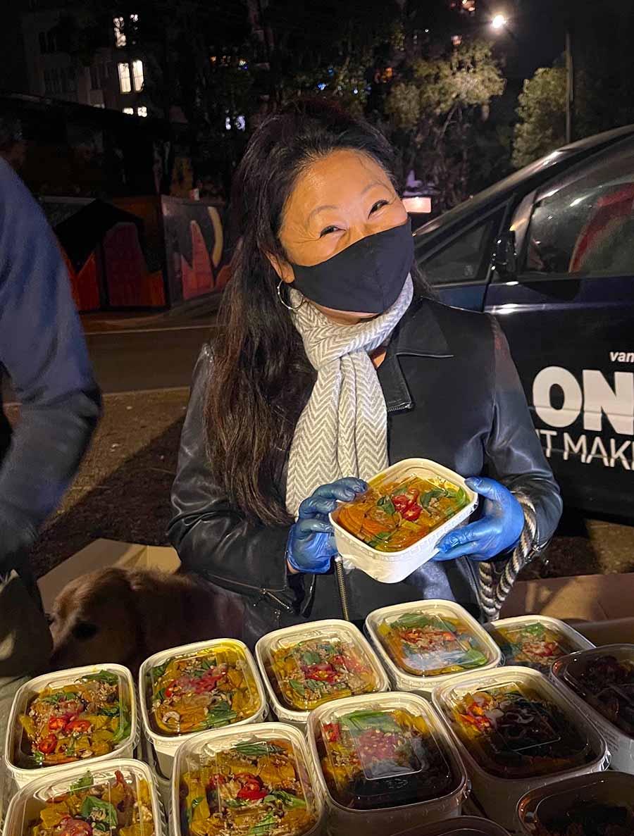Nagi Maehashi at meal distribution site, holding meal