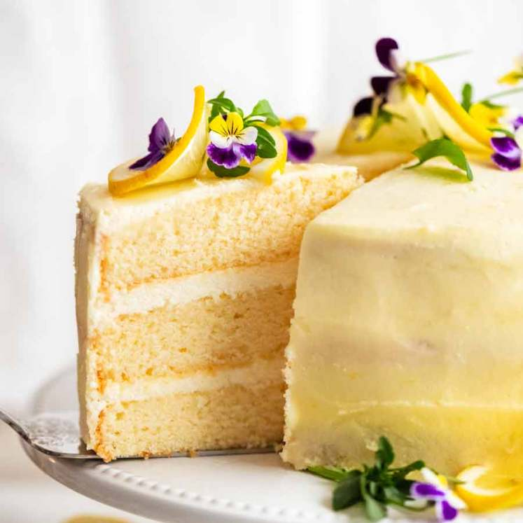 Pulling out a slice of Lemon Cake with Fluffy Lemon Frosting