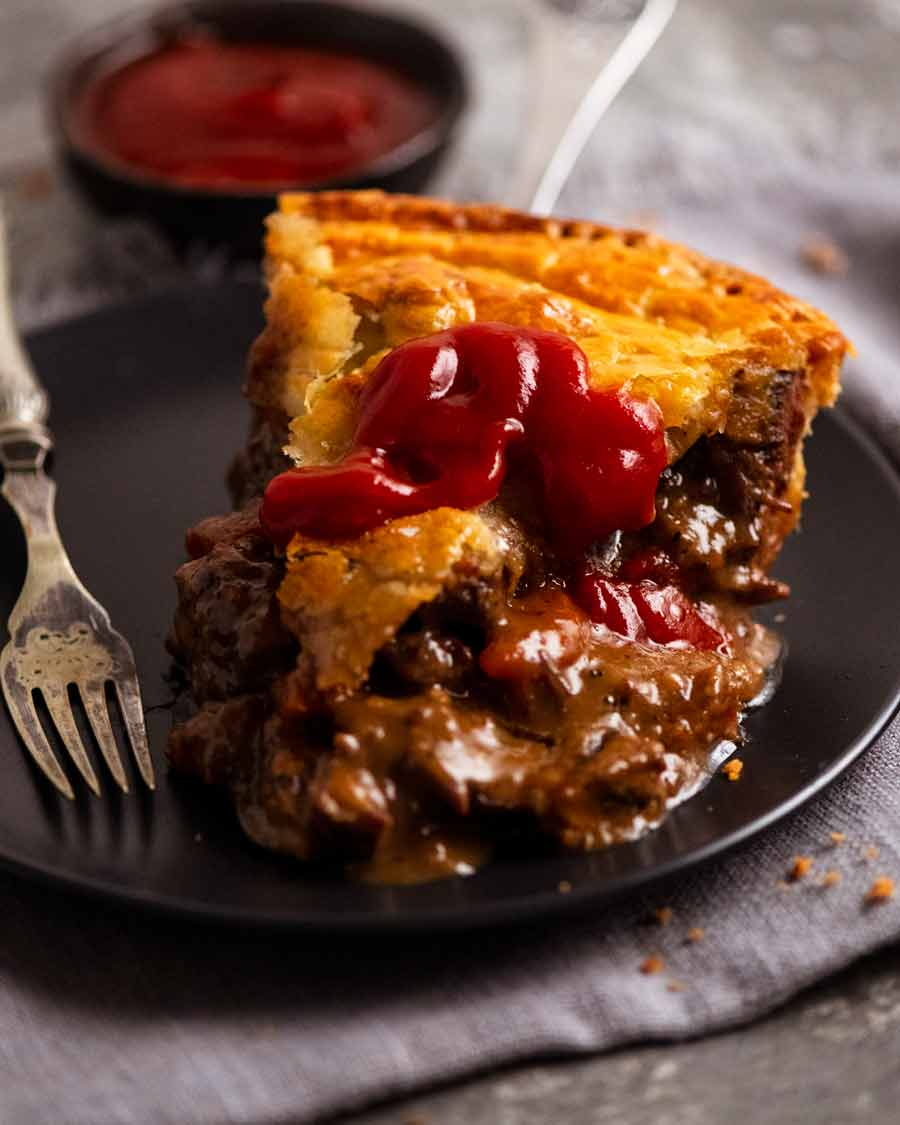 Slice of Family Meat Pie with ketchup on a plate